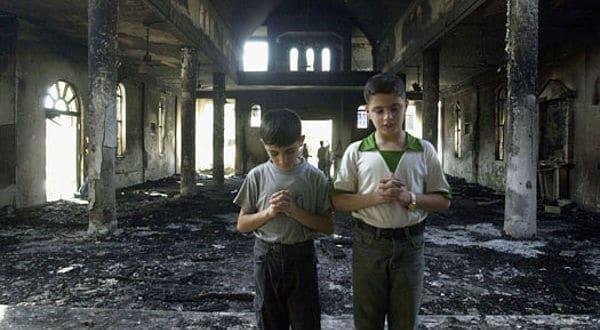 Zwei koptische Buben beten in einer von Islamisten zerstörten Kirche in Ägypten.