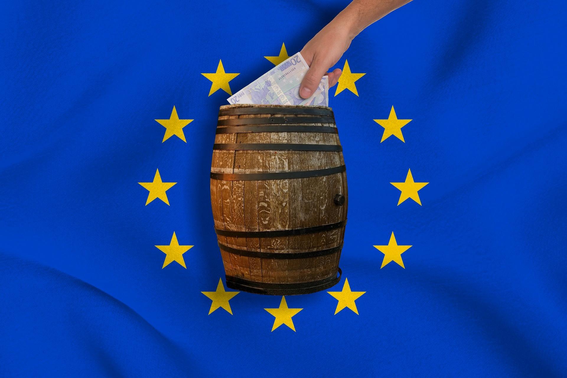 EU-Fahne mit Holzfass in der Mitte. In das Fass werden Geldscheine gesteckt. EU Fass ohne Boden. Nur durch Kürzung des EU-Haushaltes bleibt den Bürgern mehr Geld in der Tasche.