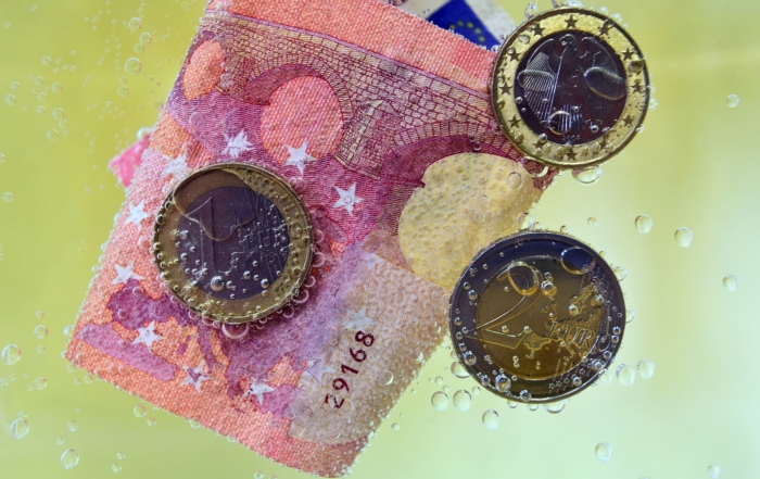 Bild: Euro-Münzen und Euro-Scheine in einer Flüssigkeit. EU-Geldwäscherichtlinien: Ursachen statt Symptome bekämpfen!